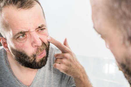 Hombre adulto investigando sus arrugas en la cara. Guy después de despertarse mirándose en el espejo. Concepto de proceso de envejecimiento. Foto de archivo