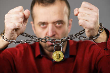 Man having problems with crypto currency. Adult guy being tied up with block chain bitcoin. Stock Photo