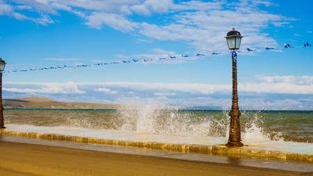Greece, sea coastline in resort village. Promenade walking area on seaside, greek flag and street lamp, Peloponnese