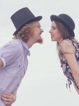 Vintage retro couple, man and woman enjoying their romantic date outside wearing fedora hats.