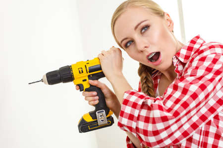 Woman having troubles with using construction drill. Female does not know how to use driller. 版權商用圖片
