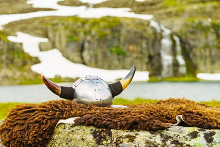Viking helmet on lake shore in Norway. Tourism and traveling concept