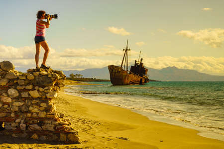 Tourism vacation and travel. Woman tourist on beach taking photo with camera, shipwreck in the background