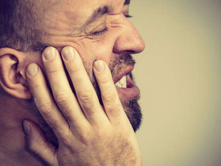 Portrait of adult man suffering from tooth pain ache. Dental problem, health issues concept. Stock Photo