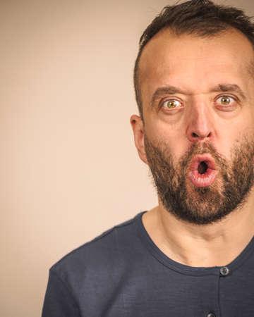 Shocked amazed beared adult guy having astonished full of disbelieve face expression. Фото со стока