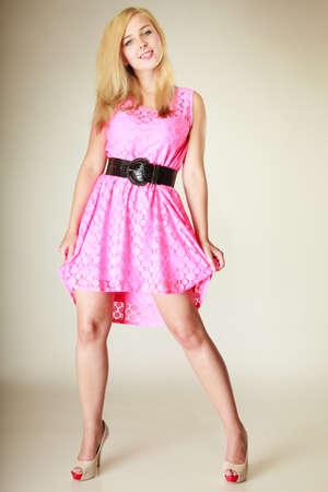 Mode, concept de vêtements. Belle jeune femme vêtue d'une robe féminine rose courte avec une grande ceinture noire. Tourné en studio sur fond blanc Banque d'images