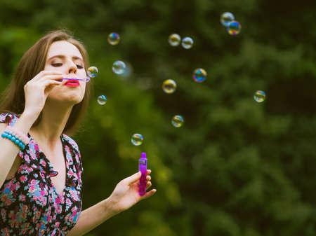Glück und sorgloses Konzept. Junge Frau, die Spaß beim Blasen von Seifenblasen im Freien im Park hat Standard-Bild
