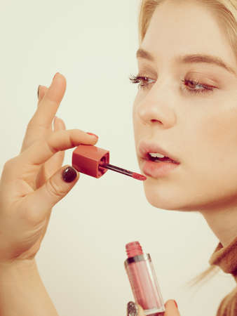 Young adult woman applying lipstick or lip gloss on her lips getting her make up done.