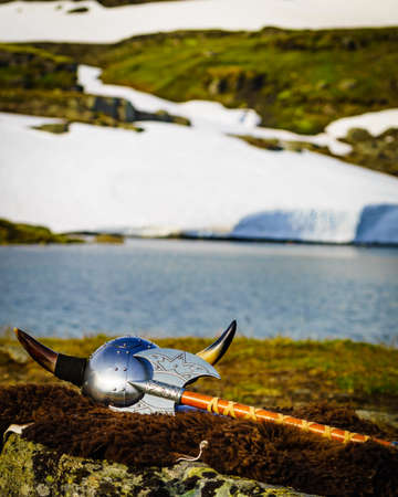 Viking helmet with axe on lake shore in Norway. Tourism and traveling concept