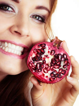 Woman cheerful brunette girl holding pomegranate fruits in hands on white. Healthy eating, cancer prevention, immune support. Stok Fotoğraf