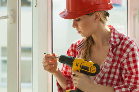 Young woman adjusting, changing her drill bit doing home renovation. Female construction worker having driller tool working on diy.