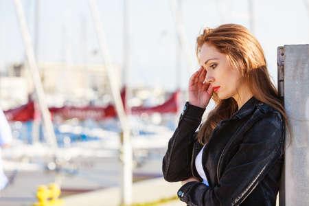 Sad unhappy young woman walking alone in city marina. Mental health, depression or solitude concept.
