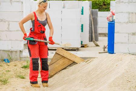 Frau, die hart auf der Baustelle arbeitet und mit der Schaufel Sandboden gräbt. Teilweise neu gebautes Haus im Frühstadium. Industrie.