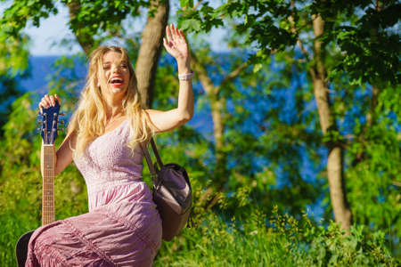 Travel vacation hitchhiking concept. Summer girl hippie style with acoustic guitar outdoor on nature
