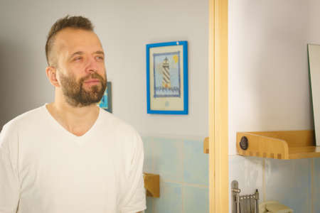 Volwassen man kijkt naar zichzelf in de badkamerspiegel. Kerel die op het punt staat zijn ochtendhygiëneroutine te doen.