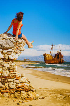 Travel freedom. Mature tourist woman on beach enjoying summer vacation. An old abandoned shipwreck, wrecked boat in the background