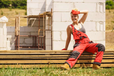 Woman in dungarees relaxing after hard work on construction site. Young female lying outdoor taking a break Banco de Imagens
