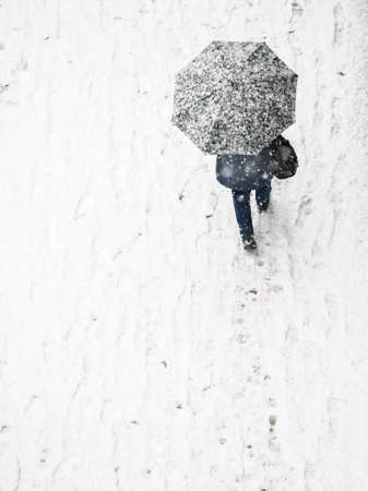 View from top at person walking on city streets during winter snowy weather. Person going through pavemet covered in white snow holding protective umbrella.
