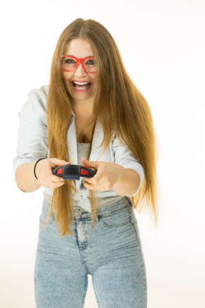 Young adult woman playing on the video console holding game pad. Gaming gamers concept.