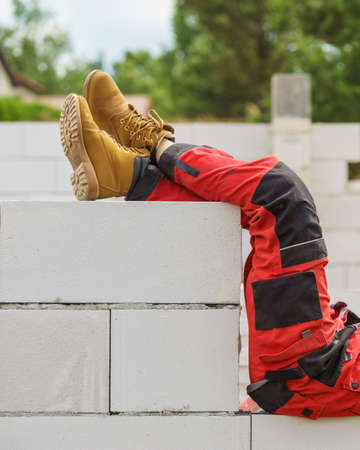 Unrecognizable person on construction site wearing protective worker red black pants trousers