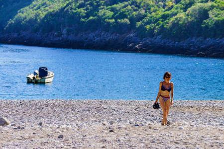 Travel freedom concept. Mature woman in swimwear on sea shore enjoying summer beach vacation. Stock Photo