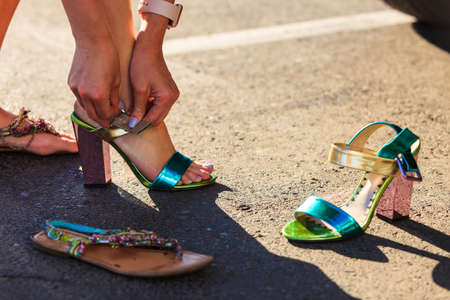 Girl changing shoes on street. Woman removing high heels and wearing flat summer sandals