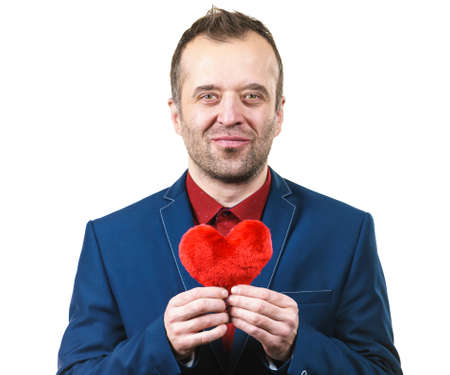 Elegant businessman wearing formal suit holding love symbol, little red heart shaped pillow. Studio shot on isolated background.