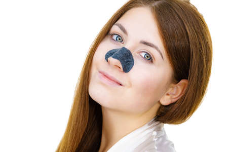 Woman appying clear-up strips on nose, using pore cleansing textile mask, against white. Girl taking care of skin complexion. Beauty treatment. Skincare. Stock Photo