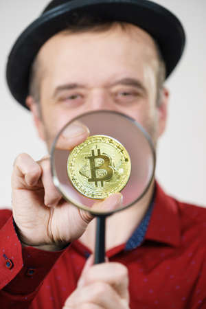 Man looking through magnifying glass at bitcoin crypto internet currency. Trying to figure out net banking