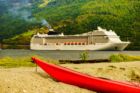 Kayak on shore and cruise ship on fjord in norwegian tourist destination Flam village.
