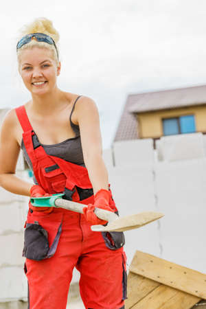 Woman working hard on construction site, using shovel digging sand soil. Partially built new home early stage. Industry.