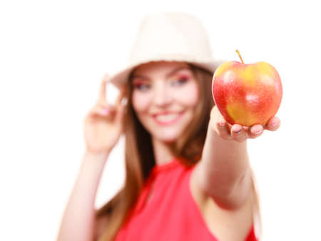 Woman charming girl long hair colorful make up wearing summer hat holds big red apple fruit. Healthy eating, vegetarian food, dieting and people concept. 写真素材