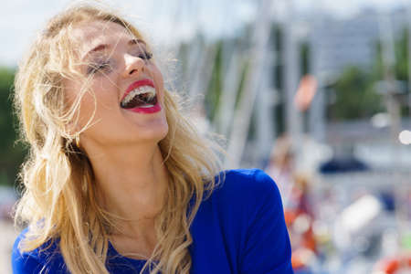 Happy joful adult fashionable woman smiling cheerfully wearing blue navy shirt and red lipstick. Imagens