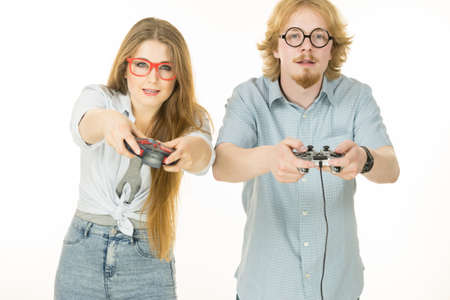 Very emotional couple enjoying leisure time by playing video games together. Studio shot isolated Stockfoto