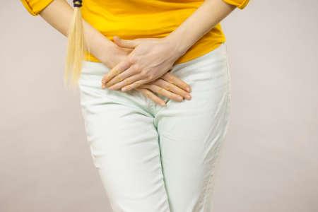 Junge kranke Frau der Nahaufnahme mit den Händen, die das Drücken ihres unteren Unterleibs der Gabelung halten. Medizinische oder gynäkologische Probleme, Gesundheitswesenkonzept