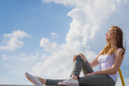 Trendy fashionable woman relaxing outdoor wearing casual footwear white sneakers and hole trousers. Female enjoy sunlight against blue sky.