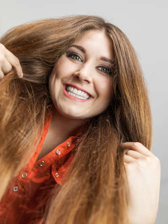 Happy positive woman with long brown hair presenting her healthy hairdo. Haircare concept. Imagens