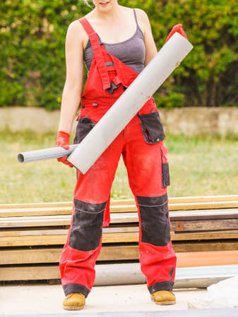 Woman in dungarees carrying plastic pipes on her home construction site, building new home. 版權商用圖片