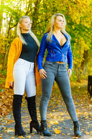 Two friends women wearing fashionable outfit. Female having navy bue leather jacket, mustard cardigan, jeans and high ankle black boots.