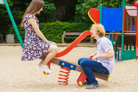 Happy funny couple having fun on playground for kids. Teenagers being on date. Reklamní fotografie