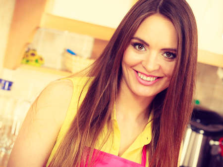 Attractive woman face housewife wearing pink apron portrait