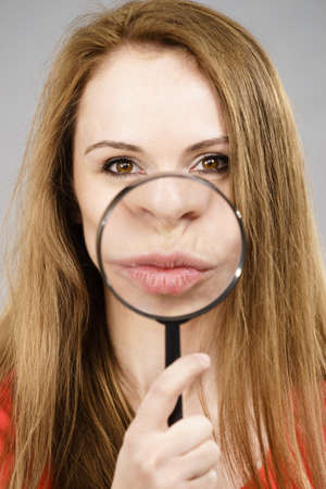Happy young woman showing big lips through magnifying glass. Lip enlargement concept.