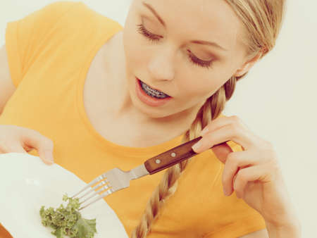 Happy young woman about to eat lettuce holding fork and smiling. Toned image colors. Stok Fotoğraf