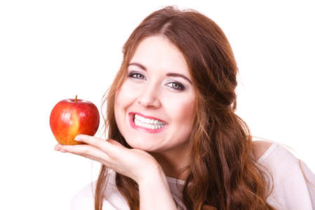 Woman holding red apple fruit in hand close to face, smiling, isolated on white. Healthy eating, high fibre diet concept. 写真素材