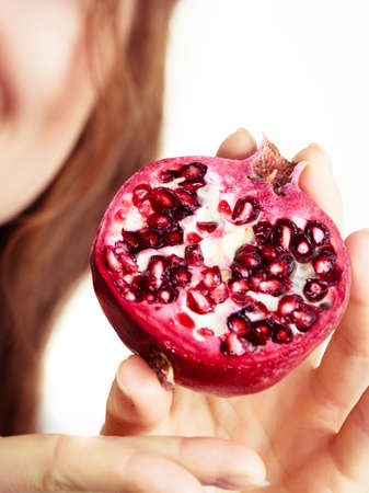 Woman holding pomegranate fruits in hand, isolated on white. Healthy eating, cancer prevention, immune support.