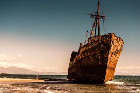 Travel. Tourist woman on beach near the famous rusty shipwreck in Glyfada beach near Gytheio, Gythio Laconia Peloponnese Greece.