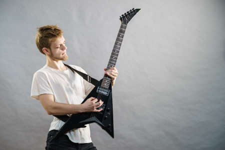 Man playing on electric guitar during gig. Musical instrument. Teenage boy having music hobby.