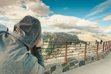 Tourism vacation and travel. Man looking through sightseeing binoculars tourist telescope, overlooking Geirangerfjord and mountains landscape from Dalsnibba viewpoint, Norway