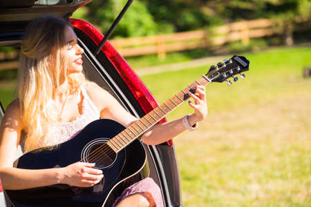Hippie looking woman wearing long skirt sitting in van vehicle camper trailer with guitar, playing peacefully music surrounded by nature. Female camping, traveling, hitchhiking Stock Photo