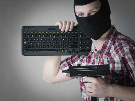 Crazy hacker man. Unrecognizable guy wearing black balaclava holding computer keyboard and gun. Hate speech on the internet. Imagens